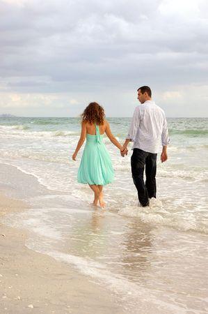 ボニータ ビーチ、フロリダ州ボニータスプリングスで水の縁に沿ってビューアーから離れて歩く若い恋人