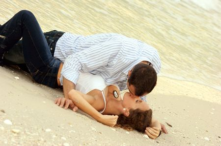 Beautiful attractive couple laying on the beach making love, fully clothed, she is in a submissive pose, his dog tags are showing but words have been made unreadable Stock Photo - 4931790