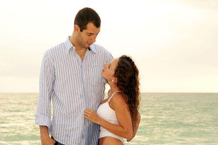Unique couple debout infron de l'océan montrant leur différence de hauteur.