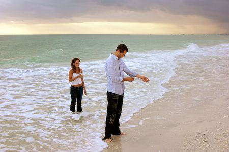 A surreal image of young couple coming out of the ocean fully dressed at sunset. The man is fixing his shirt 免版税图像