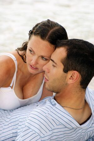 Close up of attractive couple, their heads restng together, she is all wet, they are looking to the left, ocean waves are in the background photo
