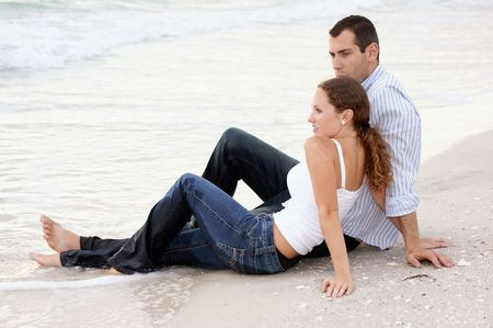 A handsome young american couple are sitting on the beach at the oceans edge, fully clothed, their clothes are wet, their feet are in the water