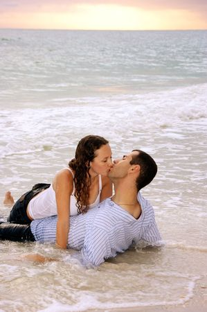 sexy couple on beach: young lovers so wrapped up in their kissing they dont notice that the tide is rising around them as the sunsets