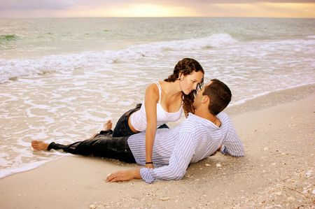 Two lovers on the beach, he is laying on his back, she is dripping wet between his legs making eye contact with him, they are wet from the ocean waves. In the background the sun is setting. Stock Photo