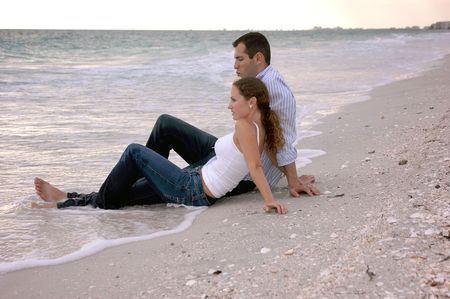 wet jeans: A young couple on vacation are  at the beach sitting in the water, fully dressed as the sun begins to set, their legs are wet.