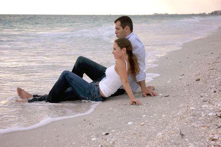 pantalones vaqueros mojados: Una joven pareja de vacaciones en la playa est�n sentados en el agua, completamente vestidos como el sol comienza a configurar, las piernas mojadas.