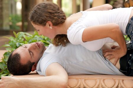 beautiful woman leaning in close  on top of man who is laying on his  back with his arms up, she is grabbing his stomach photo