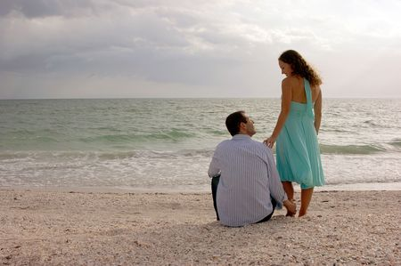 beautiful classic romantic image of young couple touching each other  and gazing into each others eyes at the beach in the gulf of mexico with the ocean in front of them. shot from behind as the sun begins to set. Plenty of copy space photo