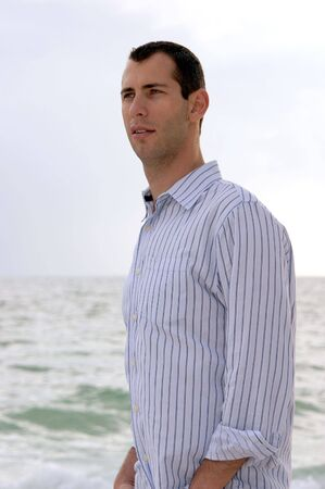 late twenties: Three quarter profile portrait of man in his late twenties, looking to the left, shot outdoors under cloudy sky, slightly diffused, with waves in the background