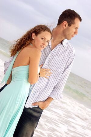 A tall young handsome man is looking out towards the ocean while his beautiful woman holds him and looks at the viewer in this beach angle shot Stock Photo - 4956487