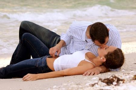 濡れた服を着て、ビーチにキスを置くことの若いカップルの美しいセクシーなイメージです。