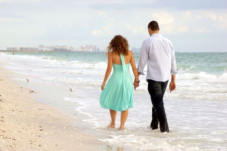 A young couple walking hand in hand along the beach, their feet ate in the water, they have their backs to the viewer, there are birds on the beach and a city in the background photo