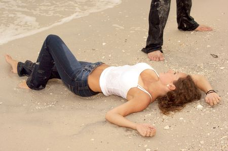 wet jeans: Beautiful sexy young woman laying on the beach in wet jeans looking up at man who is standing above her out of frame