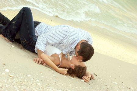 haciendo el amor: Hermosa joven que se extendi� en la playa, sus ropas mojadas y el hombre, por la que se est� en la parte superior de la mujer.