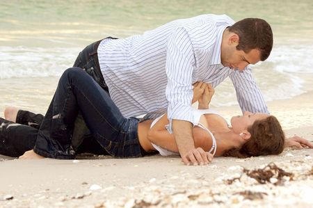 A beautiful young couple on the beach in wet clothes, the woman is laying on her back, the man is over her, she is unbuttoning his shirt. Stock Photo
