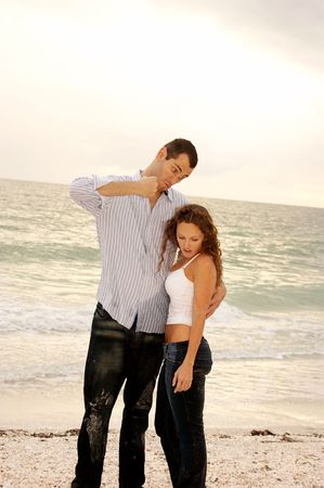 Funny image of tall man pretending he is man  and about to punch short woman in head while she ignores him at the beach
