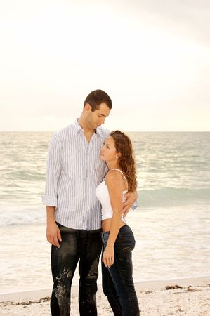 shorter: Tall handsome man looking down at shorter woman  and holding her close at the beach with ocean waves in the background. Stock Photo