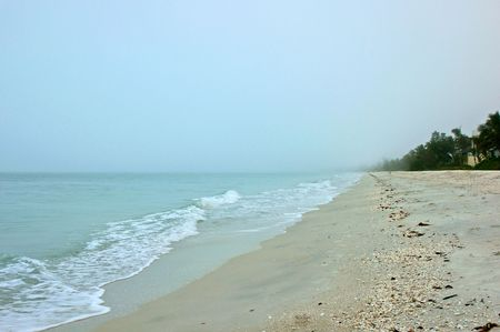 Looking down Bonita beach in Bonita Springs Florida on an early morning, fog is still in the distance.