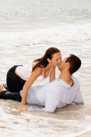 beautiful young couple  at the beach, about to kiss as the tide comes up and covers them with water, getting washed away.