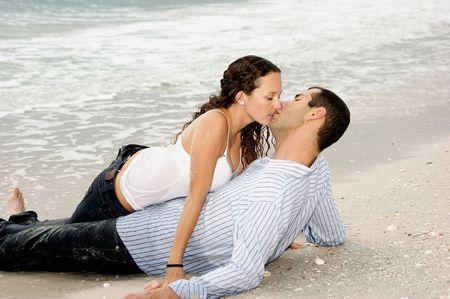 A young american couple are on the beach kissing, the woman is on top of the man photo