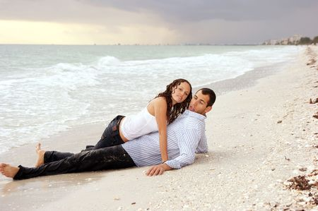 A beautiful you lady is laying on top of a man at the beach, their clothes are wet and she is looking at viewer, he has strange expression on his face at sunset. photo