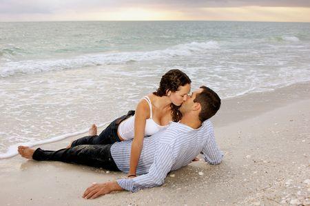 haciendo el amor: adultos j�venes joven besando en la playa como se pone el sol. Foto de archivo