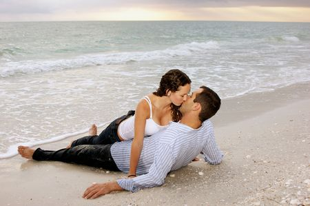 young adult couple kissing at the beach as the sun sets. Stock Photo
