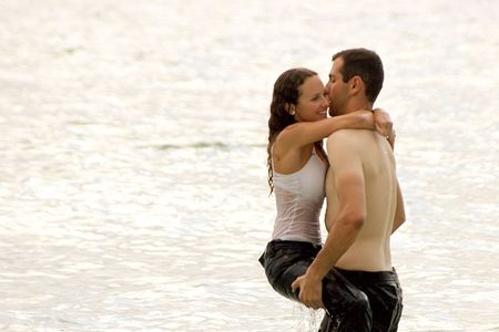 a bare chested young man is lifting a soaking wet woman from the water, she is smiling and fully clothed. photo