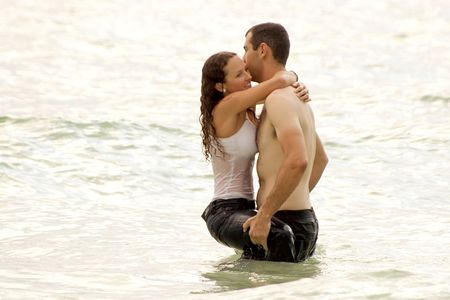 a bare chested young man is holding a soaking wet woman in the water, she is smiling, fully clothed and hugging him. photo