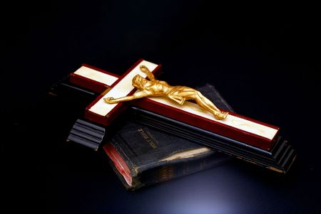 An old wooden cross with golden figure of christ is placed on top of an antique bible. With blue accent light on black background. photo