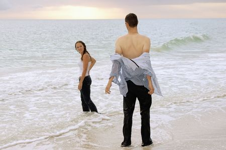 a soaked fully clothed couple are at the water's edge at the beach, the man is taking off his shirt. photo