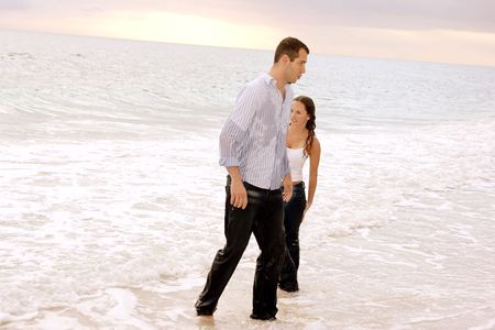a fully clothed young couple seem to be coming out of the ocean, unhappy and soaking wet. photo