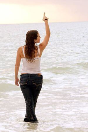 a shapely young woman is standing in the ocean fully clothed and soaking wet pointing up to the sky wth her feet crossed