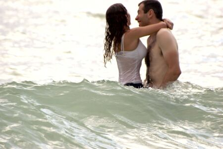 young couple playing in the ocean, hugging and laughing and being engulfed by the waves. photo