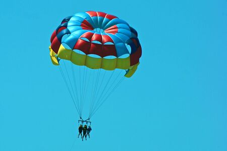 a multicolored parasailing parachute in the sky with three passengers Stock Photo
