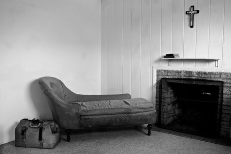 run down: run down room with old sofa and travel bag. There is also a fireplace and a crucifix hanging above the shelf which has two books on it.