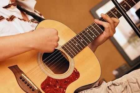 hand position: Joven de jugar la posici�n de la mano de mostrar de guitarra ac�stica y tocaba Foto de archivo