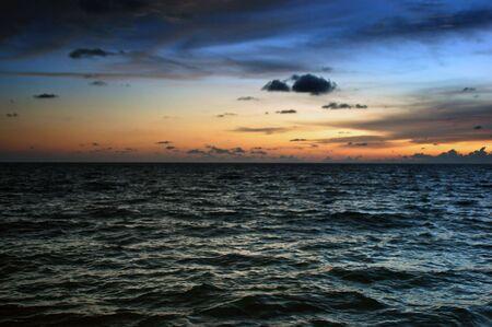encrespado: un cielo de m�ltiples colores en la puesta de sol con nubes en los diversos agitado olas del mar.