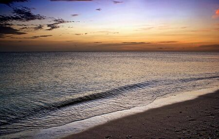waves gently rolling to shore under a vivid sunset