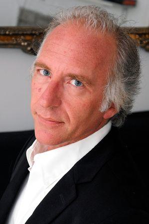 第 3 四半期に直面するハンサムなプロフェッショナルな青い目をした年上の男の肖像画。
