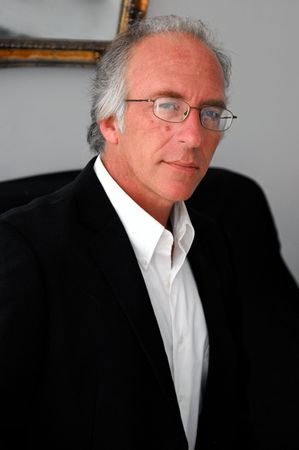 man sitting looking at viewer wearing glasses a white dress shirt and black suit coat photo