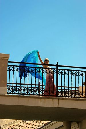balcony: beautiful woman looking down from balcony, waving with long blue cloth in hand. wearing long pink dress and sunglasses with room for text