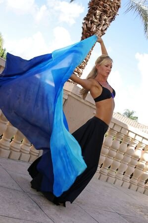 arching: pretty blonde belly dancer in black arching back while dancing outside on balcony