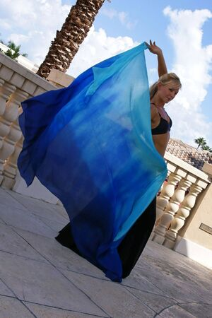 Sexy blonde belly dancer outside on balcony in the tropics holding blue veil behind her looking at viewer. photo