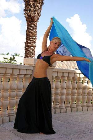 blonde woamn dancer in black top and long skirt belly dancing with blue silk veil photo