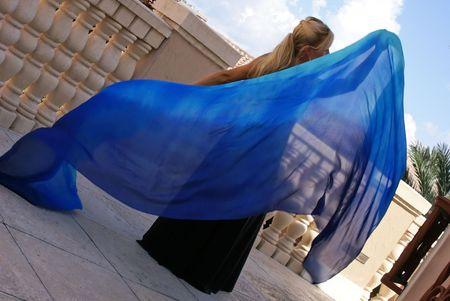 blonde belly dancer holding  blue veil behind her creating space for text or copy photo