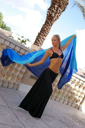 pretty and fit blonde belly dancer in black skirt with silk veil dancing outside on balcony photo