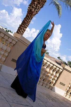 beautiful blonde belly dancer wrapped in blue veil looking at viewer photo