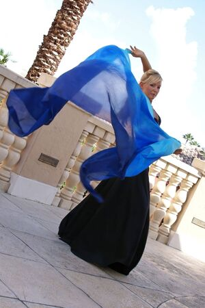 attractive blonde belly dancer in black with blue veil blowing in the wind behind her, looking at viewer. photo