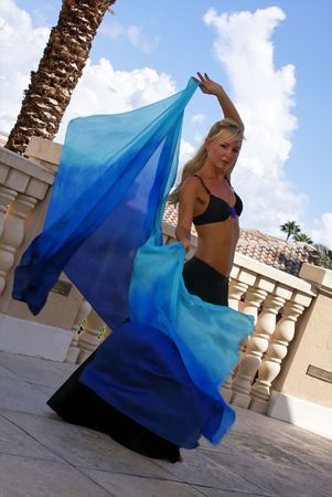 sexy blonde belly dancer in black bra and long skirt dancing on outside balcony with veil billowing out behind her making eye contact with viewer. photo